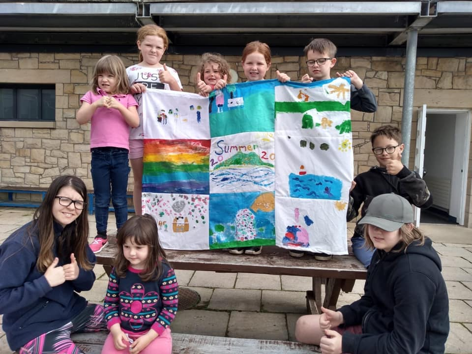 Youngsters with their flag made from individual paintings.