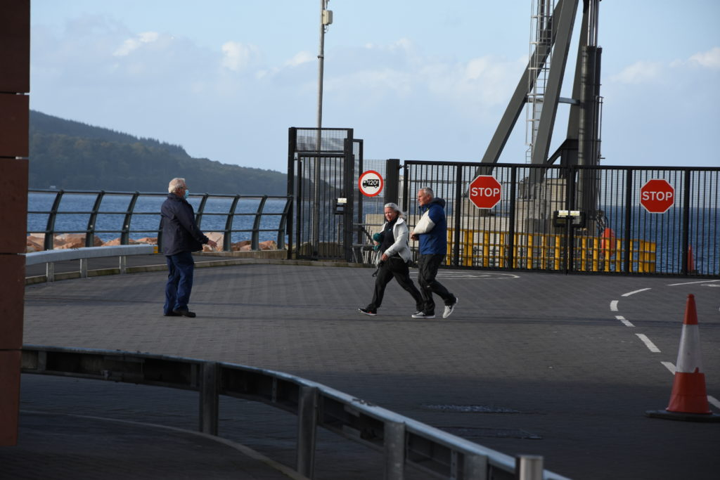 A walking wounded passenger with his arm in a sling makes his way to the ferry terminal.