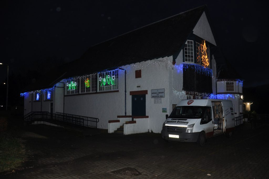 Brodick village Hall is illuminated with festive lights adorning the building.