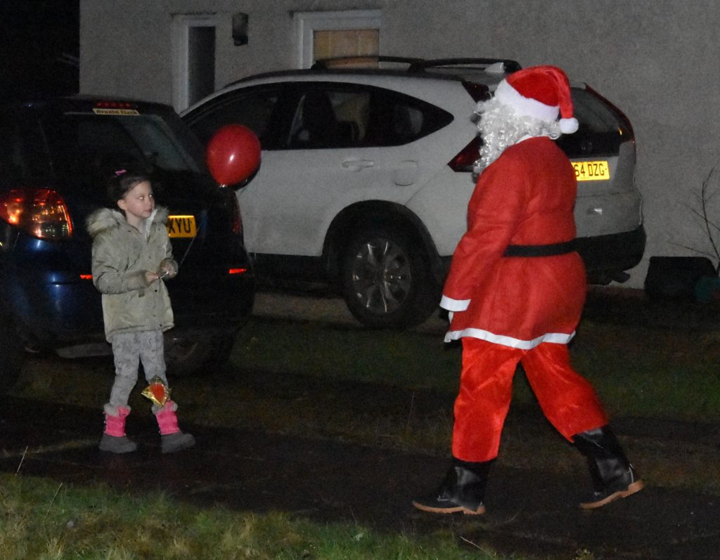 A girl chats to Santa outside her house.