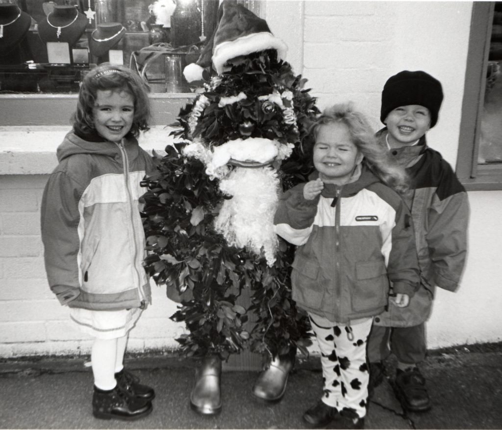 Tabitha and Fabienne Robertson-Burnett and their friend Mungo Paul with Mr Christmas Tree outside the Arran Craft Gallery in Brodick.