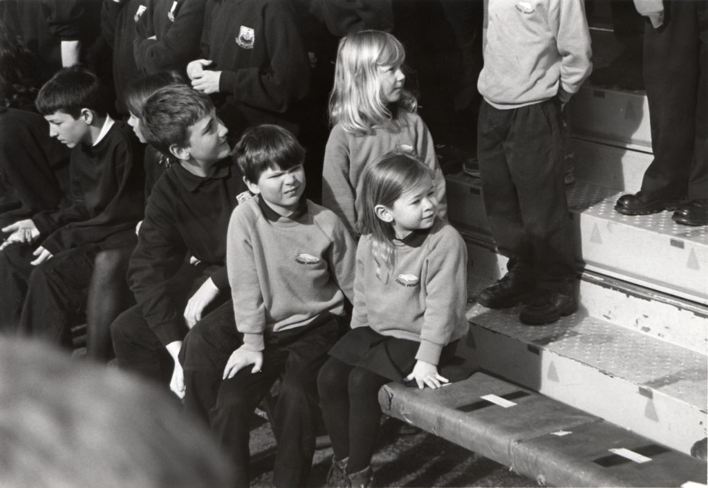 Some of the youngest pupils take their seats at the front.
