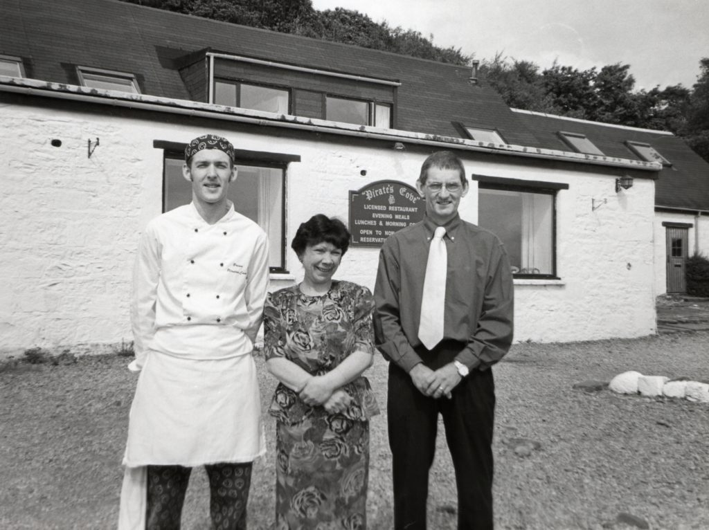 Pirate's Cove is celebrating after winning a place in the prestigious guidebook The Taste of Scotland. Owners Godfrey and Sue Hall celebrated the achievement with chef Brian Gracie. 01_B24ABTYA01
