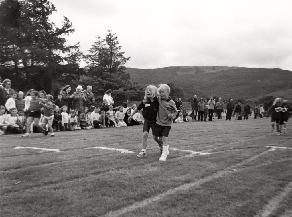 Two pupils stroll to victory in the three legged race during the Primary School Sports day.