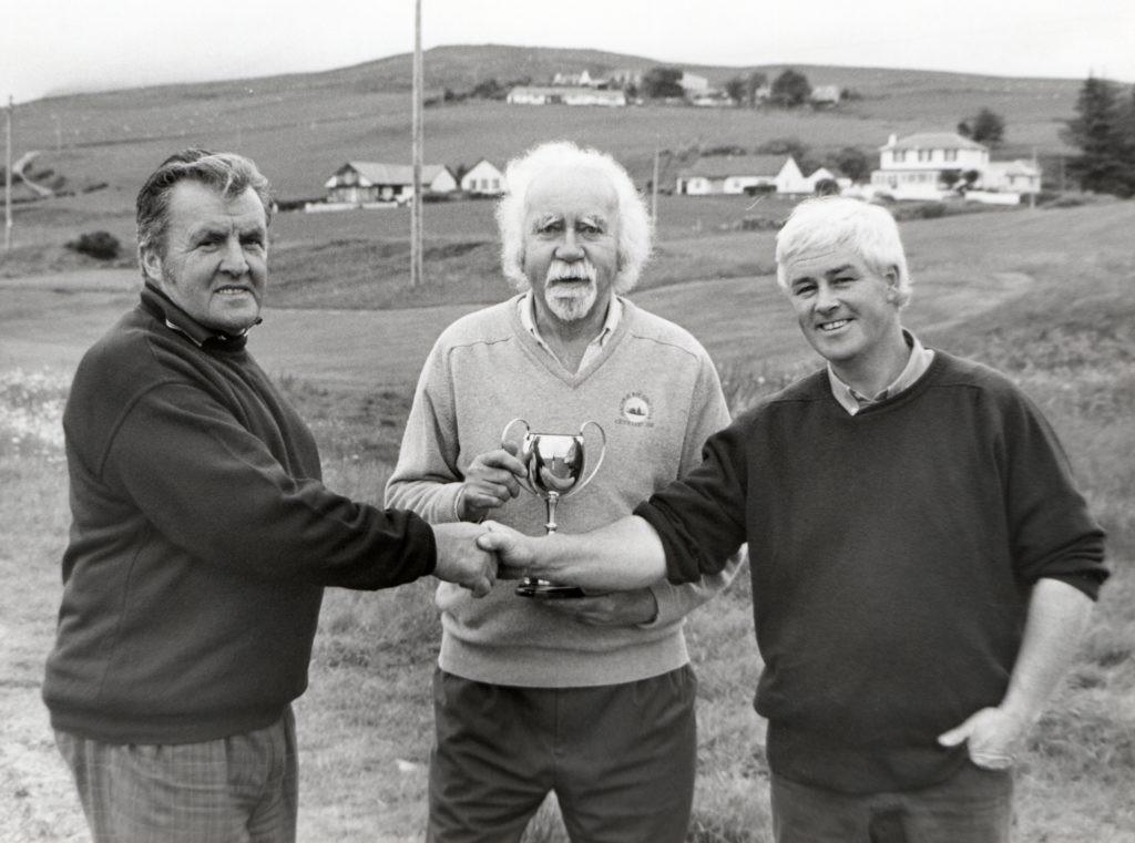 Eddie Cannon congratulates Donald Logan on his victory in the Machrie Bay Club Championship while club captain Paul Emsley stands at the ready to present the trophy.