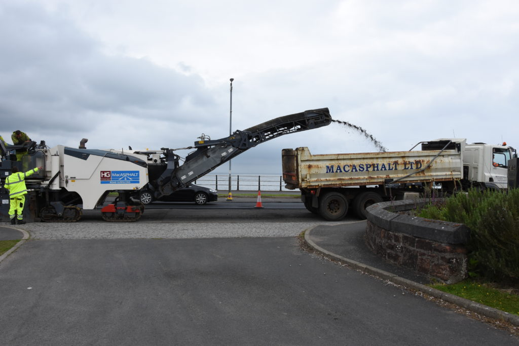 Asphalt is removed from the road surface and deposited into awaiting lorries.