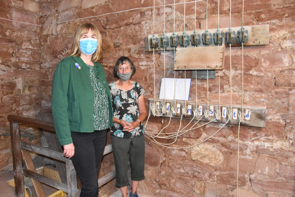 Alison and Maureen beside the bell ringing mechanism in the bell tower.