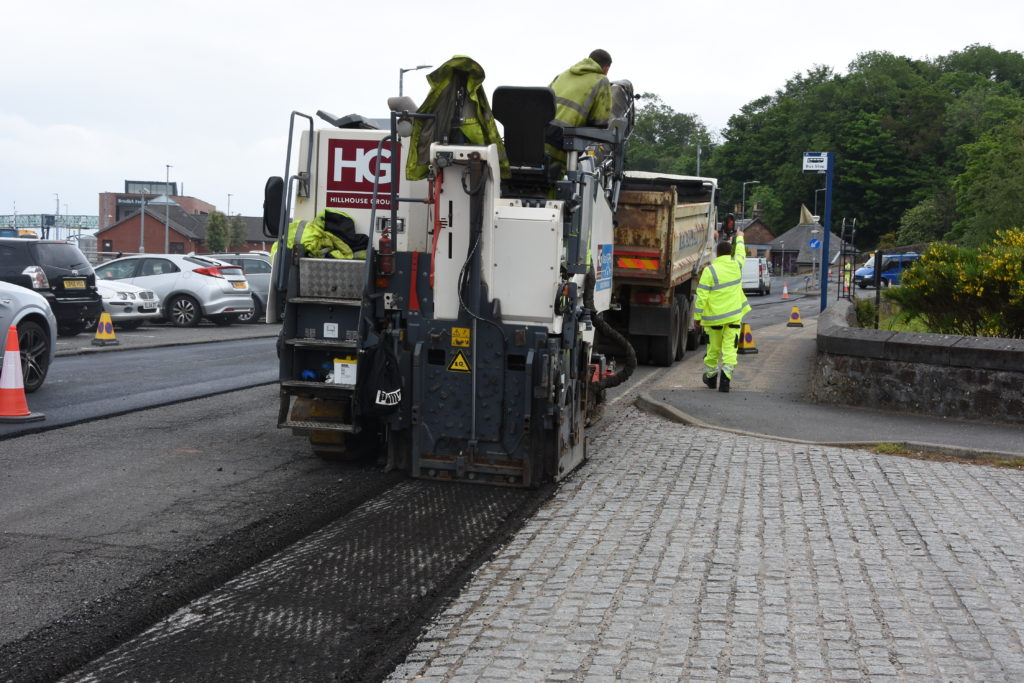 Heavy machinery grinds away the road surface which is then renewed.