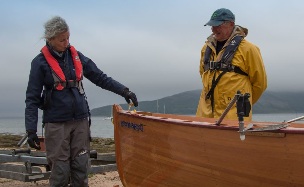 Cecilia Paul, chair of Arran Coastal Rowing Club, names and launches Moonshine in the traditional manner while boat builder, Rory Cowan looks on.