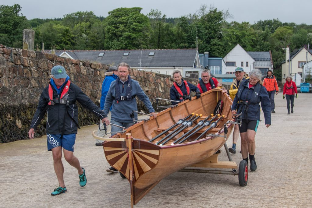 Coastal rowers and boat builder walk Moonshine down to the water for her maiden voyage.