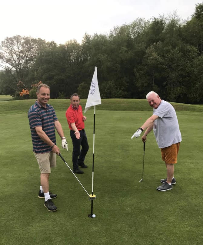 Angus Raeburn removes his ball (Covid style) from the 7th hole following his recent hole in one. Looking on are Nicol Hume and Jim Reid.