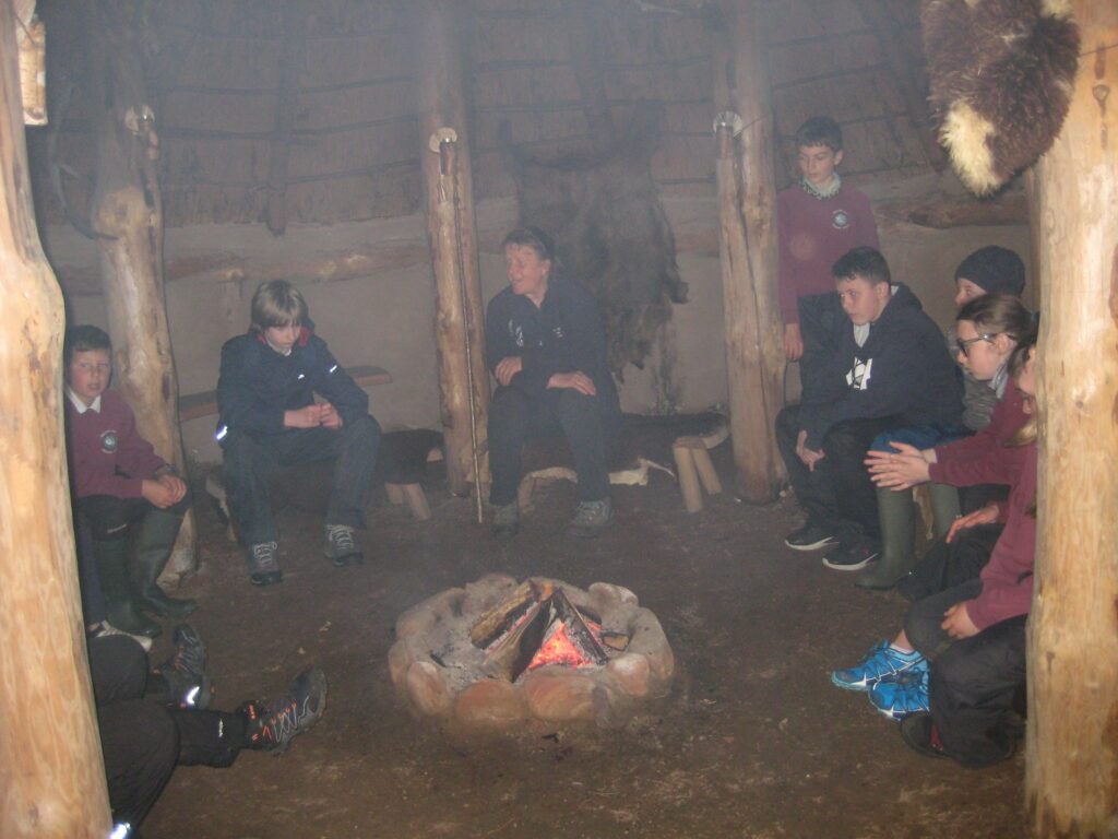 Pupils learn about how their ancestors lived in the recreated roundhouse at Brodick Castle.