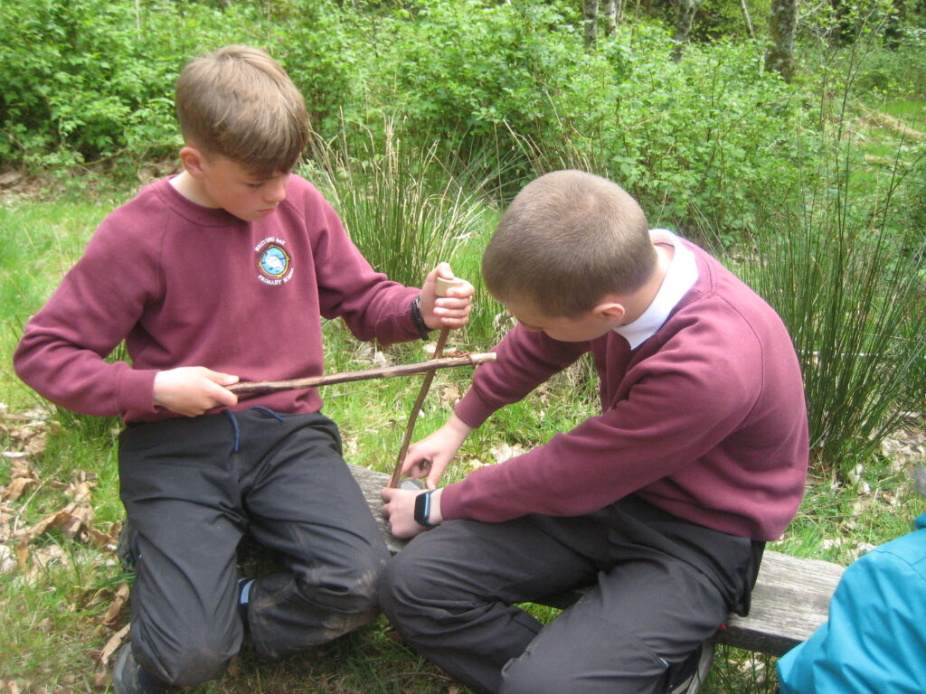 Students make shale pendants with a bow drill.