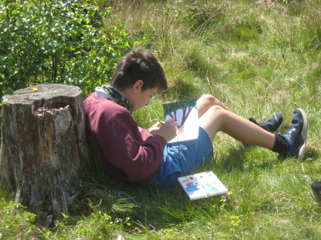 A pupil enjoys the sunshine while painting a nature scene.