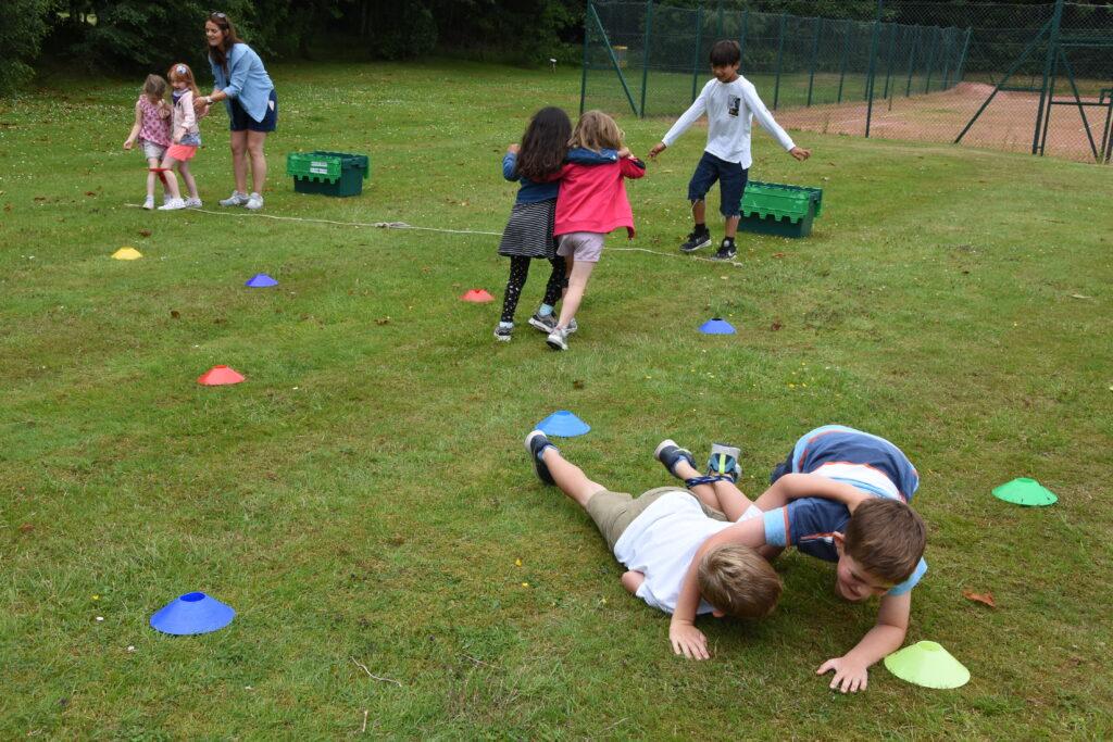 Two boys take a tumble in the three-legged race.
