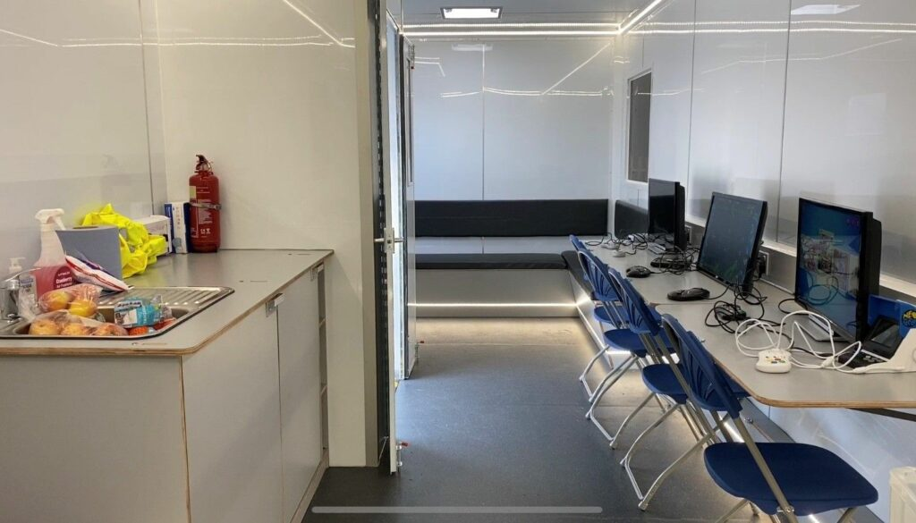 The interior of the mobile youth hub showing a bank of computers for online access.
