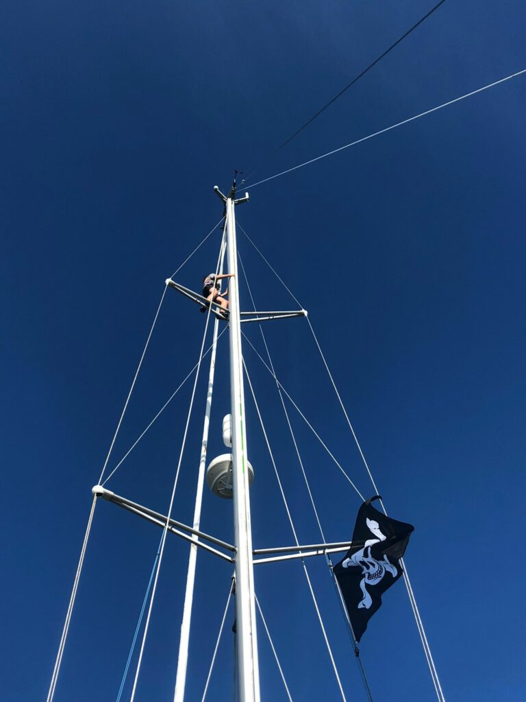 A youngster climbs to the top of the mast.