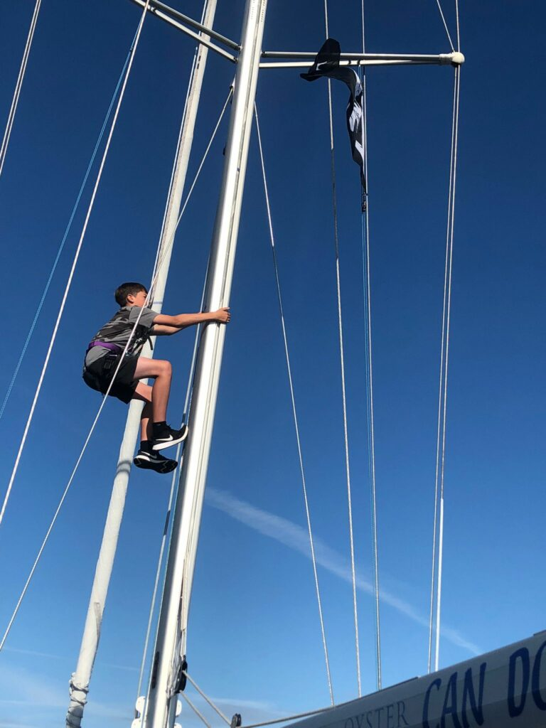 A young sailor makes his way up the mast.