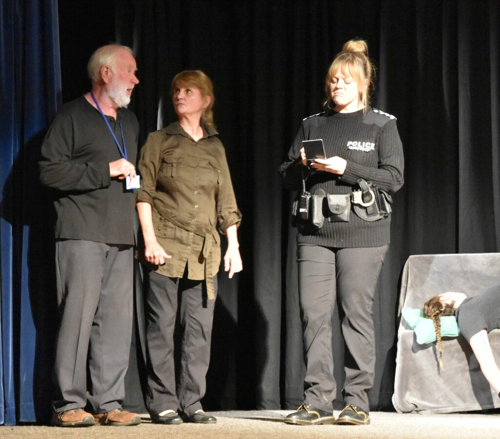 A policewoman, Stacey Gordon, questions two of the burglars.
