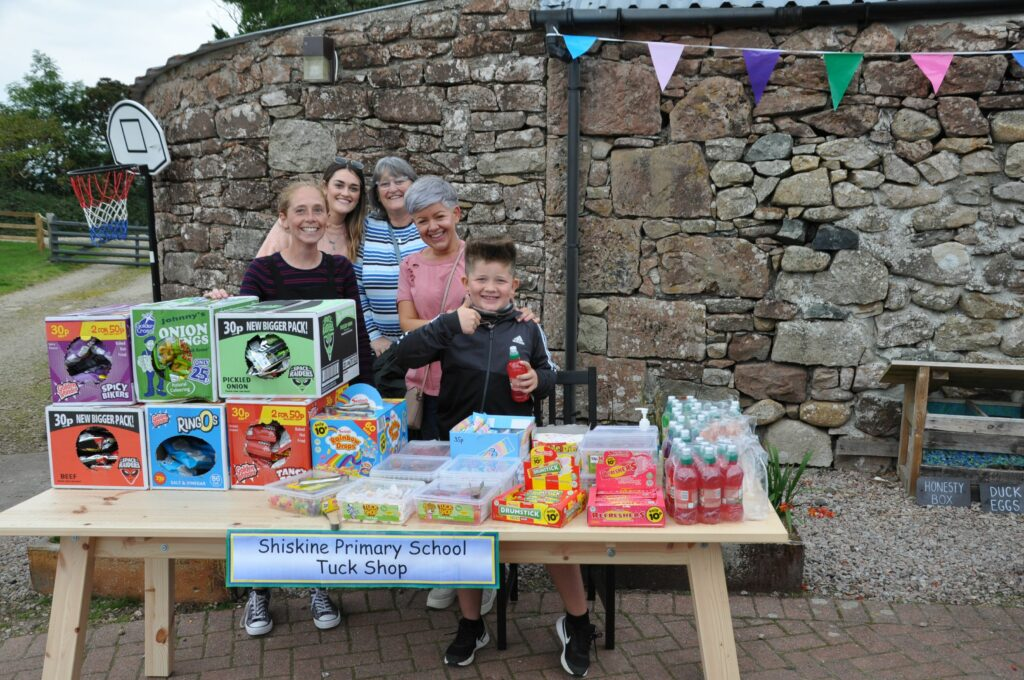 The welcoming faces of adults and children operating the Shiskine Primary tuck shop.