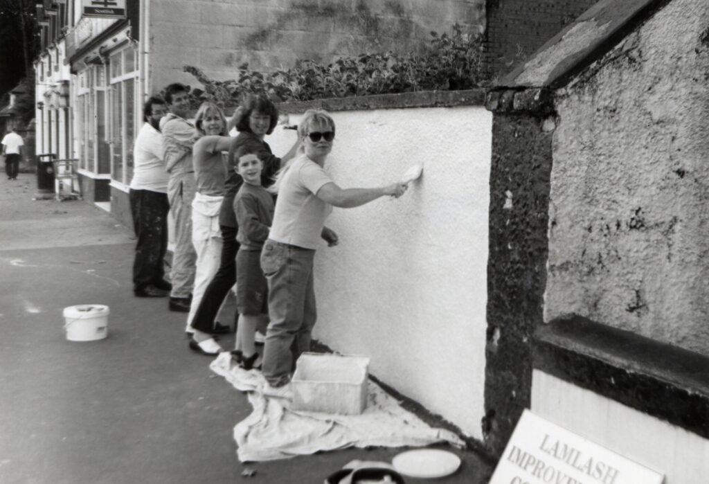 Lamlash Improvements Association volunteers apply a coat of cream masonry paint to the wall between the Aldersyde and the Co-op after becoming fed up with the tatty paintwork.