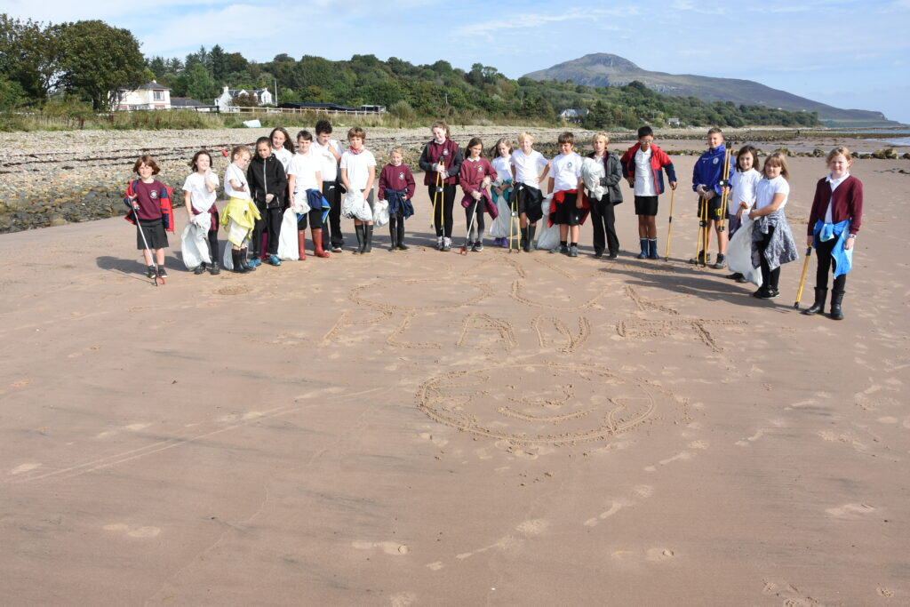 The beach cleaners from Whiting Bay primary in front of a 'save our planet' slogan written in the sand.