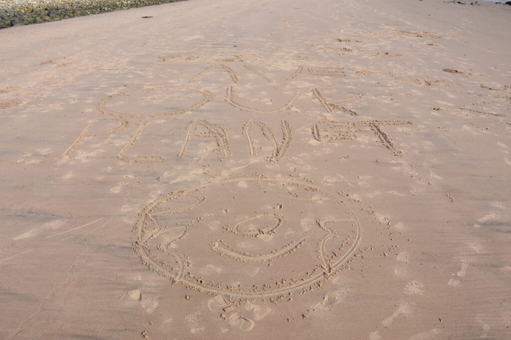 The 'save our planet' slogan in Whiting Bay with a happy planet smiley face.
