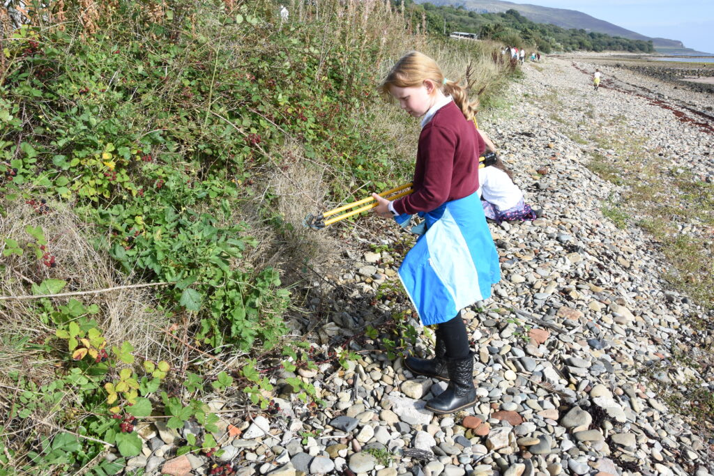 A pupil picks litter from the undergrowth.
