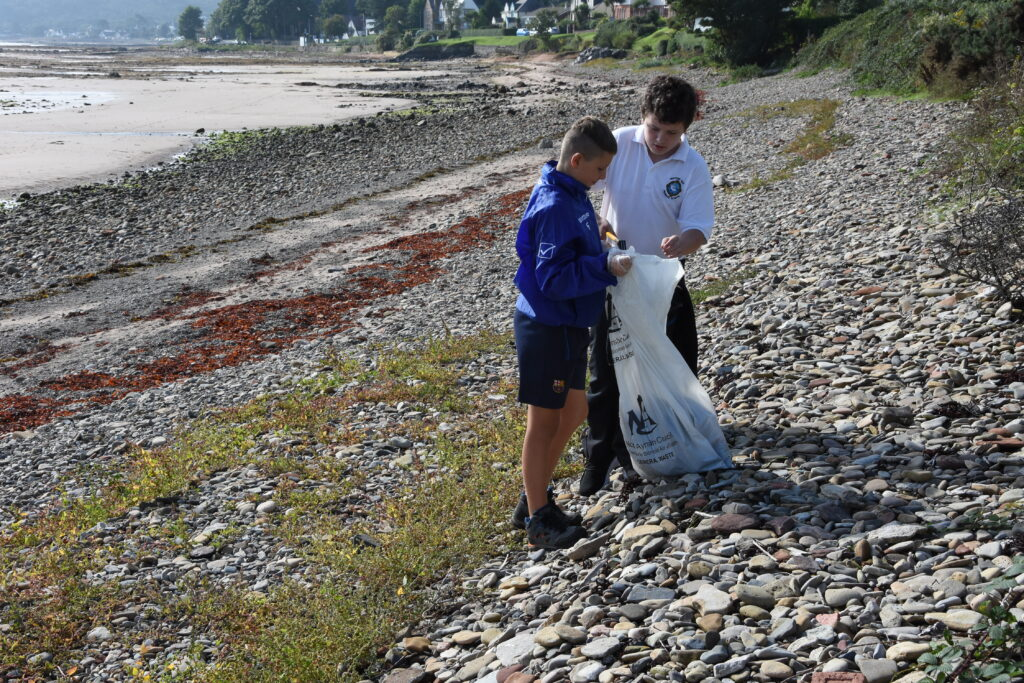 Two boys bag the litter they have found on the beach.