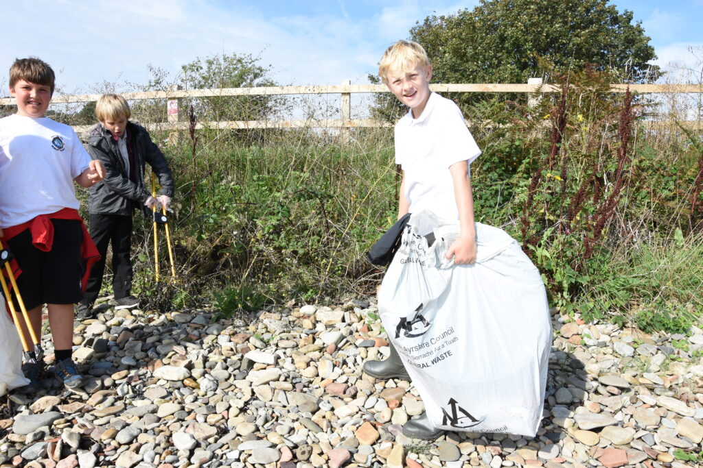 A youngster has his bag filled with a tyre - one of the largest items found on the beach clean.