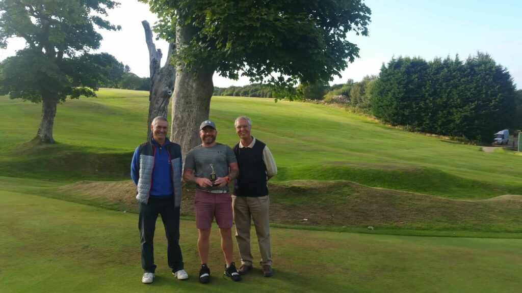 J C Reid Trophy winner Mark West and runner-up John Pennycott and club captain Stan Rainey.