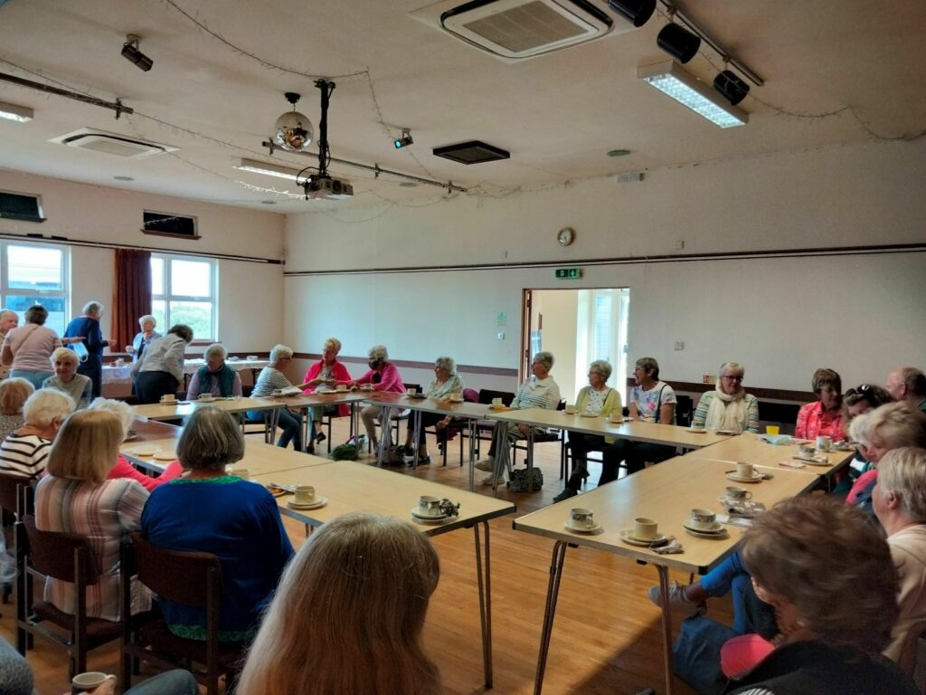 Guests and Corrie and Sannox SWI members enjoy tea and cakes.