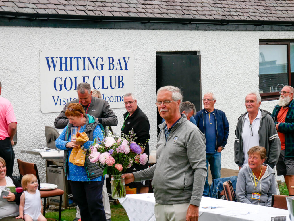 Whiting Bay Golf Club captain Stan Rainey valiantly tries to sell the last item in the auction.