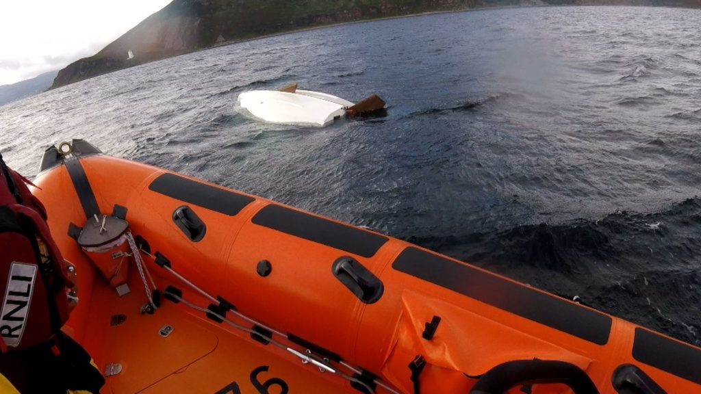 Two rescued by lifeboat from capsized dinghy