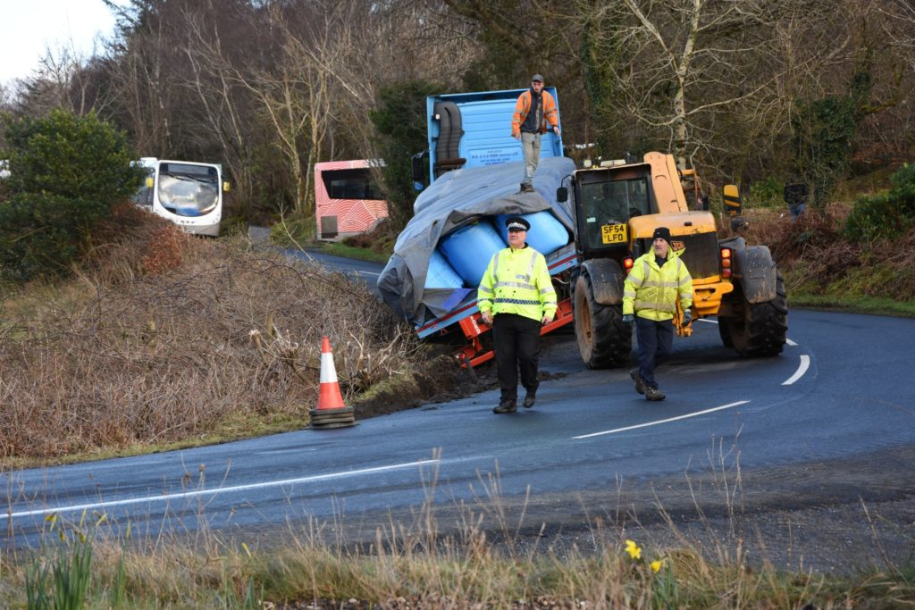 Lorry slips from road at sharp bend