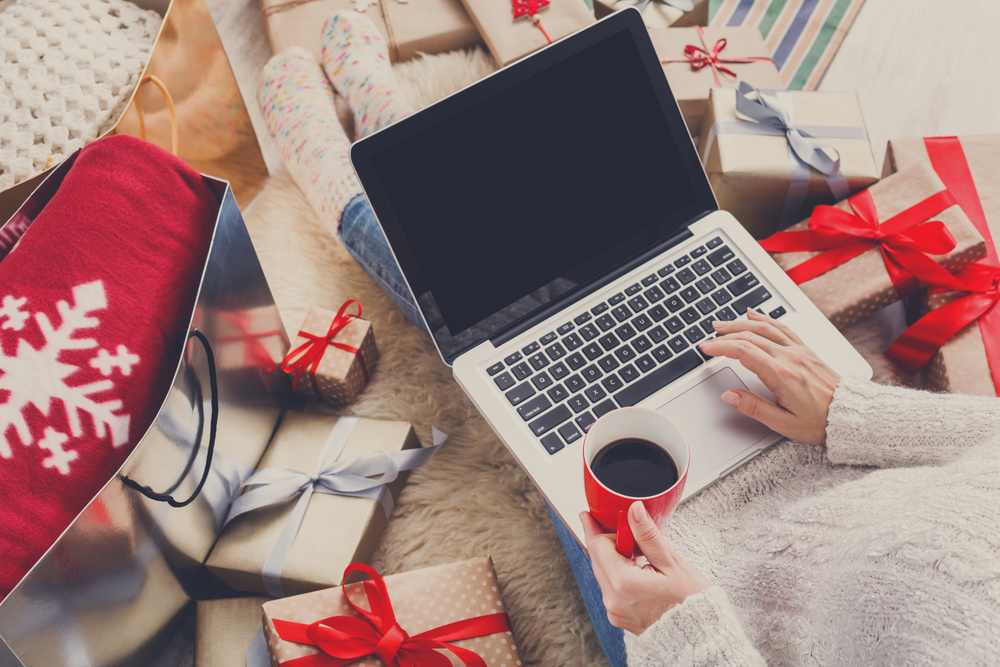 Christmas Shopping tips. Woman typing on laptop, surrounded by wrapped gifts