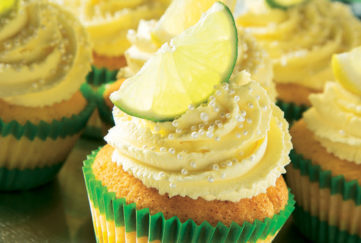 Cupcakes with gin and tonic whipped cream on the top with lemon wedges