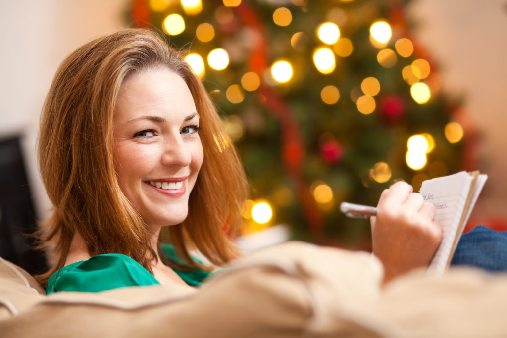 Woman sitting by Christmas tree, writing a list in a notebook