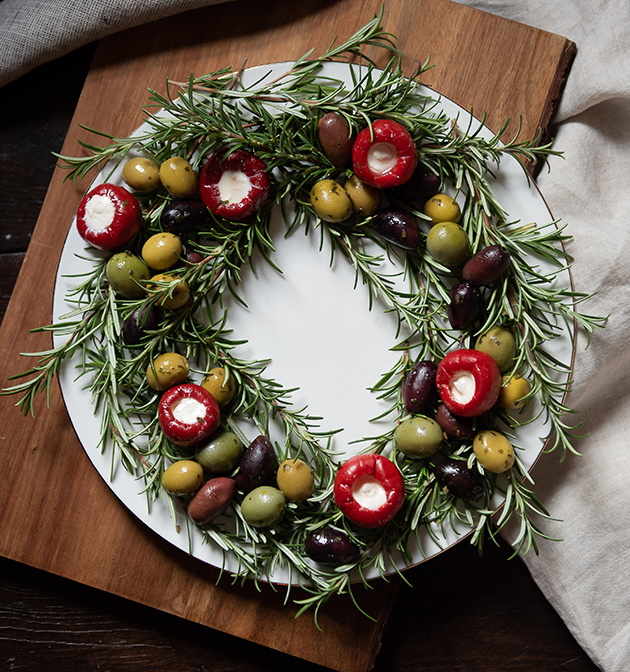 Serving wreath made of rosemary, olives and stuffed peppers