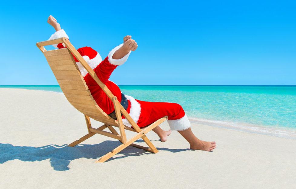 Christmas Santa Claus hands up enjoy sun on deck chair Pic: Istockphoto