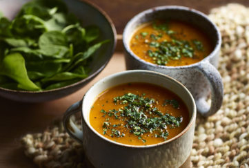 WW recipe: 2 earthenware cups of spiced carrot & ginger soup, garnished with herbs, bowl of fresh spinach on the side