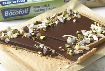 Smooth chocolate tart, decorated with toasted coconut and green pistachios, in baking tray with long, narrow triangular slices cut across the width