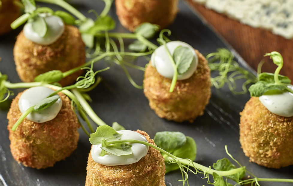 Tray of small, round breadcrumbed croquettes, each with a blob of Saint Agur blue cheese puree, decorated with pea shoots