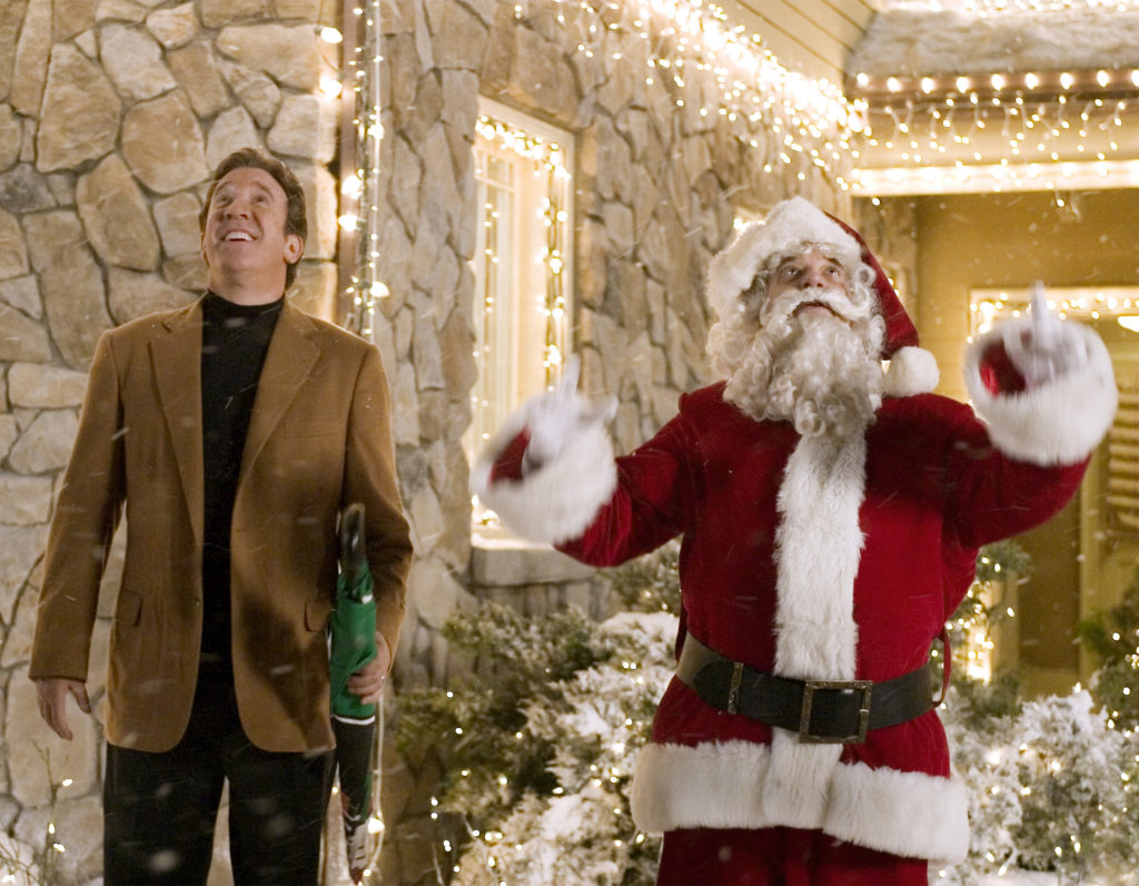 Scene from Christmas With The Kranks, Tim Allen and Santa standing outside house covered in icicle lights looking up at the sky