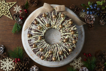 Rocky Road wreath, solid chocolate ring drizzled with white chocolate, studded with gold dusted chocolate sweets and garnished with a fabric bow