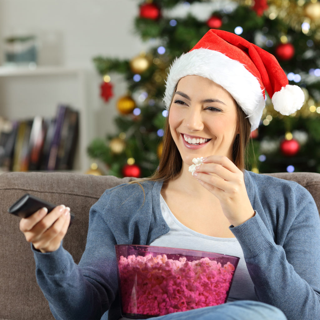 Woman in santa hat with big bowl of popcorn smiling watching Christmas TV