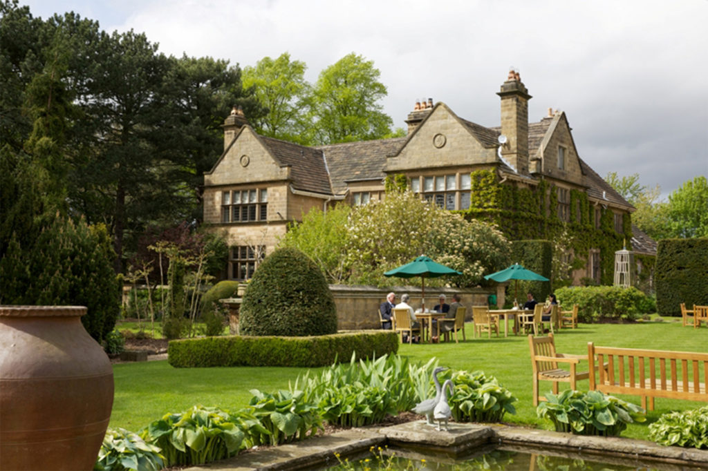 Yellow stone manor house with mullioned windows, seen from the garden with topiary, mature trees and a rectangular stone edged pond. Guests sit at tables under green fabric parasols.