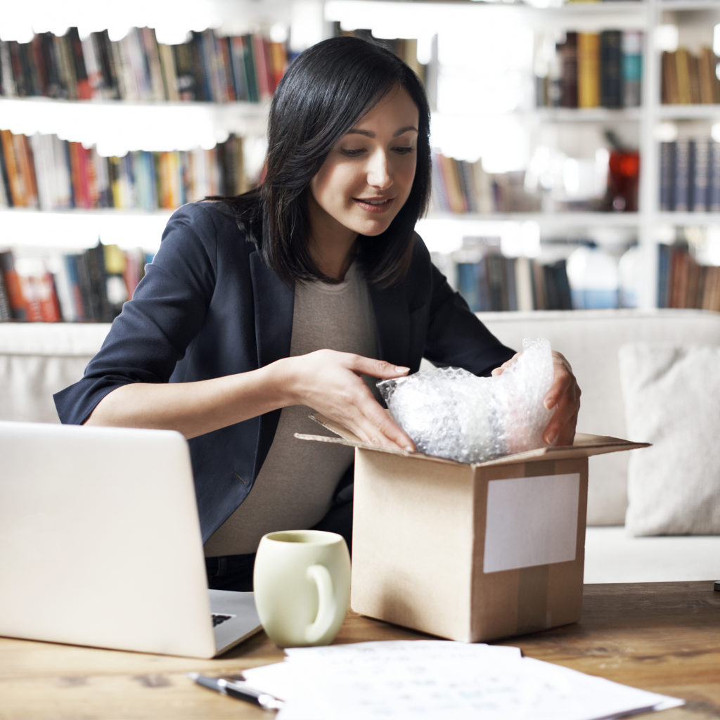Elegant 20-something woman lowering bubble wrapped item into box ready for posting