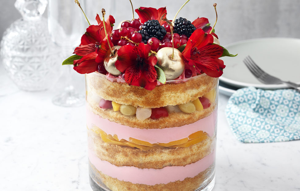 10 layered trifle in deep glass dish with sponge, pink custard, fruit cocktail and topped with flowers, berries and cherries covered in gold