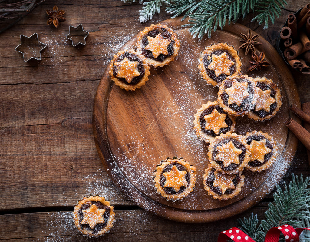 Home made mince tarts each with a pastry star on top, scattered over a round wooden board, star anise and cinnamon on the side